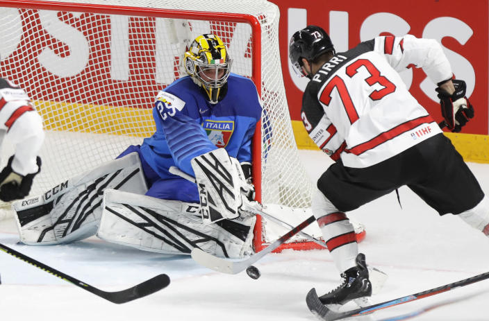 Canada's Brandon Pirri, right, challenges for the puck with Italy's goaltender Davide Fadani during the Ice Hockey World Championship group B match between Italy and Canada at the Arena in Riga, Latvia, Sunday, May 30, 2021. (AP Photo/Sergei Grits)