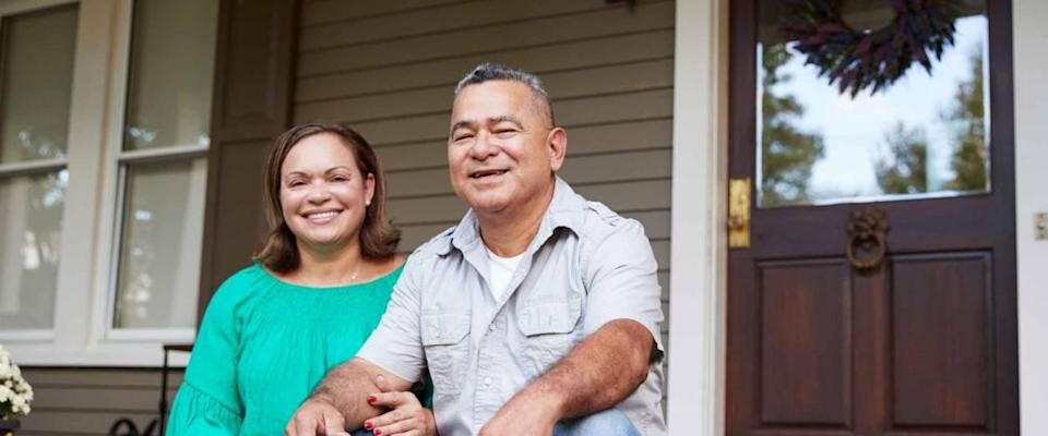 Portrait Of Smiling Senior Couple Sitting In Front Of Their Home