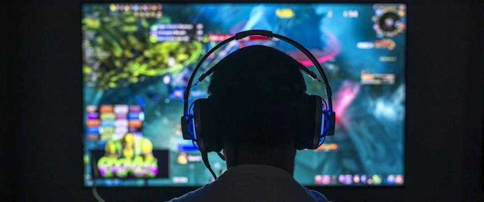 Young gamer playing video game wearing headset in the dark