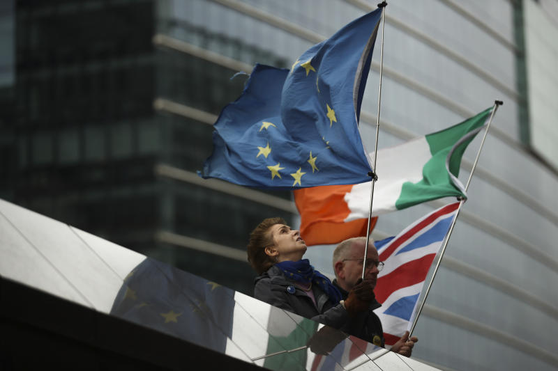 """Two anti-Brexit people hold EU, Ireland and Union Flags stand outside the European Commission in Brussels, Friday, Oct. 11, 2019. EU negotiator Michel Barnier says that he had a """"constructive meeting"""" with British Brexit envoy Stephen Barclay and underscored the cautious optimism since Thursday's meeting between British Prime Minister Boris Johnson and his Irish counterpart Leo Varadkar. (AP Photo/Francisco Seco)"""