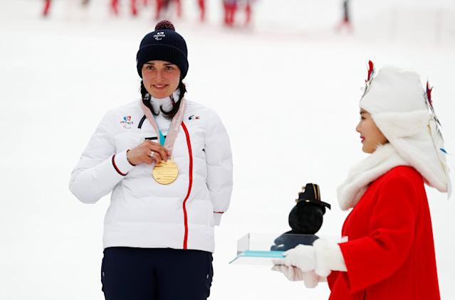 Alpine Skiing - Pyeongchang 2018 Winter Paralympics - Women's Slalom - Standing - Jeongseon Alpine Centre - Jeongseon, South Korea - March 18, 2018 - Marie Bochet of France wears her gold medal as a medal host girl walks past. REUTERS/Paul Hanna
