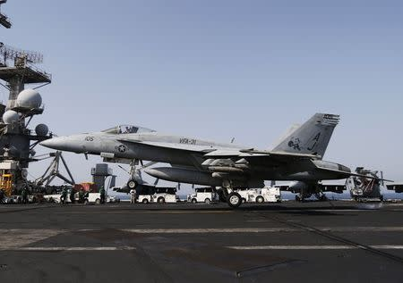 A F/A-18E Super Hornet of Strike Fighter Squadron (VFA-31) gets arrested in the landing gear onboard the flight deck of the aircraft carrier USS George H.W. Bush (CVN 77), in the Gulf August 12, 2014. . REUTERS/Hamad I Mohammed
