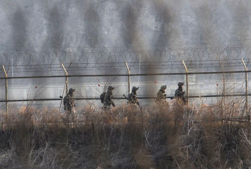 """South Korean Army soldiers patrol along a barbed-wire fence near the border village of Panmunjom in Paju, South Korea, Sunday, March 31, 2013. North Korea warned South Korea on Saturday that the Korean Peninsula had entered """"a state of war"""" and threatened to shut down a border factory complex that's the last major symbol of inter-Korean cooperation. (AP Photo/Ahn Young-joon)"""