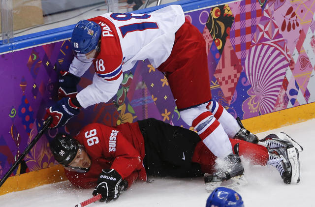Switzerland forward Damien Brunner and Czech Republic forward Ondrej Palat crash the boards in the second period of a men's ice hockey game at the 2014 Winter Olympics, Saturday, Feb. 15, 2014, in Sochi, Russia. (AP Photo/Petr David Josek)