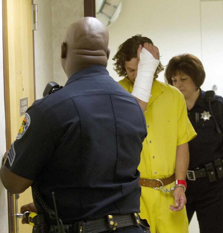 Dylan Dougherty-Stanley hides his face as he is escorted to court in Pueblo, Colo., on Monday, Aug. 15, 2011. The filing of charges against the three fugitive siblings captured in Colorado has been delayed until next week. (AP Photo/Pool, Mike Sweeney)