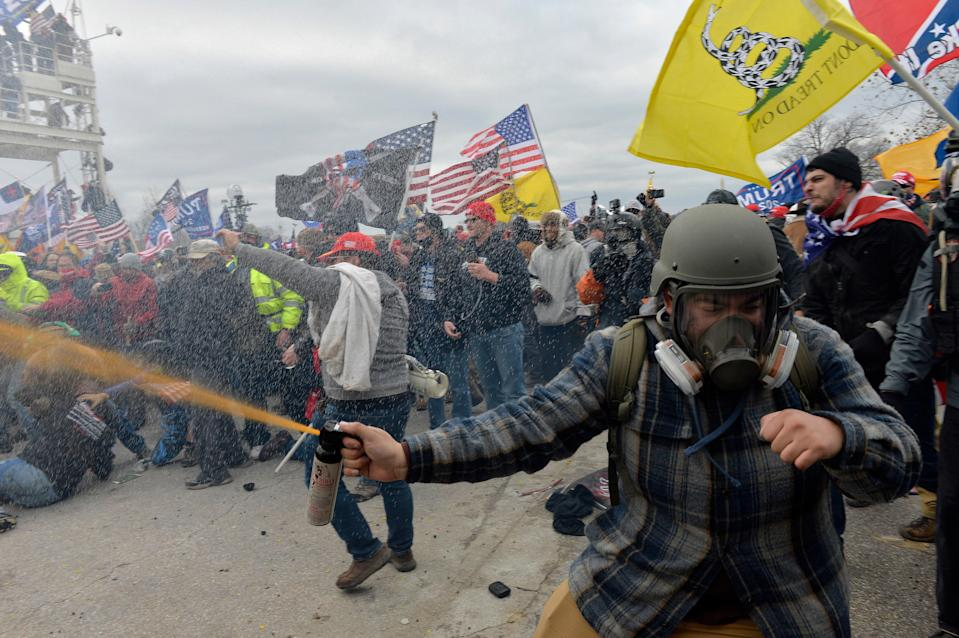 A rioter wearing a gas mask and helmet clashes with security forces at the Capitol, January 06, 2021.