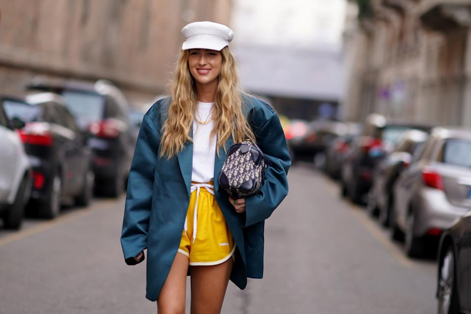 MILAN, ITALY - FEBRUARY 21: Emili Sindlev wears a white cap hat, a green oversized blazer jacket, a white t-shirt, a Dior monogram bag, yellow shorts, outside Sportmax, during Milan Fashion Week Fall/Winter 2020-2021 on February 21, 2020 in Milan, Italy. (Photo by Edward Berthelot/Getty Images)
