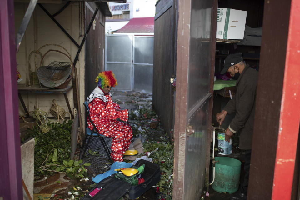 Belhussein Abdelsalam, a Charlie Chaplin impersonator puts on a clown outfit in a flower shop as he prepares to start a new day of work, in Rabat, Morocco, Thursday, Dec. 31, 2020. When 58-year-old Moroccan Belhussein Abdelsalam was arrested and lost his job three decades ago, he saw Charlie Chaplin on television and in that moment decided upon a new career: impersonating the British actor and silent movie maker remembered for his Little Tramp character. (AP Photo/Mosa'ab Elshamy)