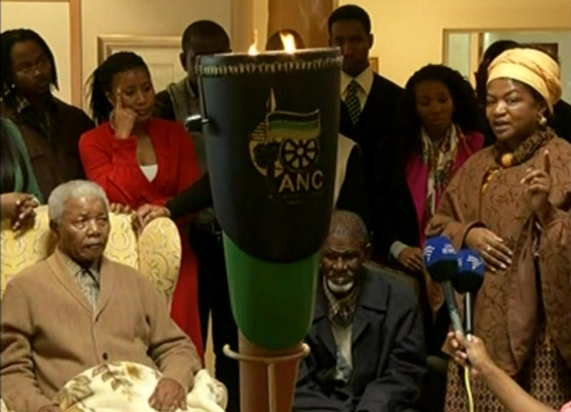 This video image taken from SABC television shows South Africa's former president Nelson Mandela, left, receiving a torch to celebrate the African National Congress' centenary from ANC chairperson Baleka Mbete, right, in Mandela's home village Qunu in rural eastern South Africa Wednesday May 30, 2012. Nelson Mandela's African National Congress brought its centenary celebrations to his home village in rural eastern South Africa. (AP Photo/SABC via AP video) SOUTH AFRICA OUT