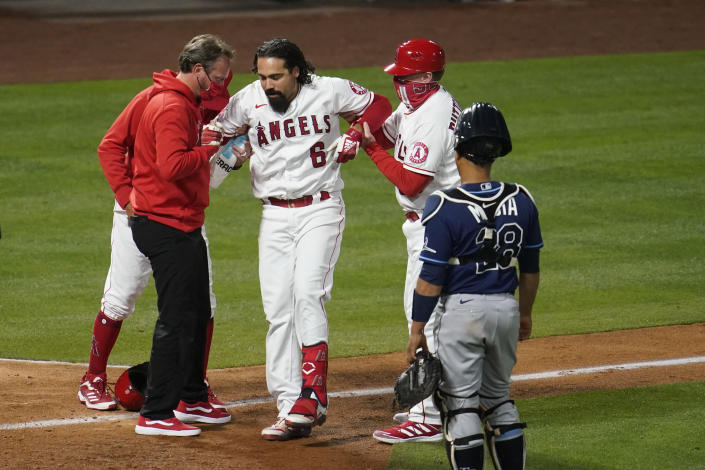 Los Angeles Angels' Anthony Rendon (6) is helped up after hitting a foul ball off his leg during the eighth inning of a baseball game against the Tampa Bay Rays Monday, May 3, 2021, in Anaheim, Calif. (AP Photo/Marcio Jose Sanchez)