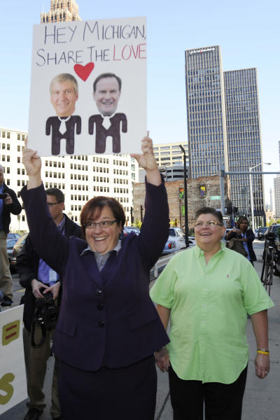 April DeBoer, left, and Jayne Rowse protest at the federal courthouse in Detroit on Wednesday, Oct. 16, 2013. The protest is in support of a federal lawsuit involving same-sex couple DeBoer and Rowse who are seeking to overturn Michigan's ban on gay adoption and same-sex marriage. (AP Photo/Detroit News, David Coates) DETROIT FREE PRESS OUT; HUFFINGTON POST OUT