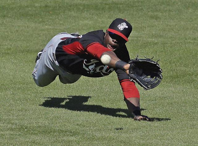 Cincinnati Reds' Roger Bernadina makes a diving try but cannot catch a ball hit by Milwaukee Brewers' Rickie Weeks during the fifth inning of an exhibition spring baseball game on Saturday, March 15, 2014, in Phoenix. Weeks singled on the play. (AP Photo/Morry Gash)