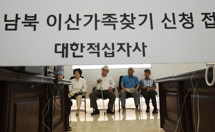 """FILE - In this Aug. 24, 2013 file photo, South Korean applicants for the reunions wait for the announcements of the names of South Korean candidates who could meet their North Korean relatives in upcoming family reunions at the headquarters of Korea Red Cross in Seoul, South Korea. North Korea has indefinitely postponed reunions of families separated by the Korean War that had been set to start Wednesday, Sept. 25, 2013. The North's statement Saturday, Sept. 21, 2013 didn't provide specifics on its decision but accused unidentified conservatives in Seoul of seeking confrontation with Pyongyang. North Korea routinely makes such claims. The Korean writing reads """" Applications reception of separated families."""" (AP Photo/Ahn Young-joon, File)"""