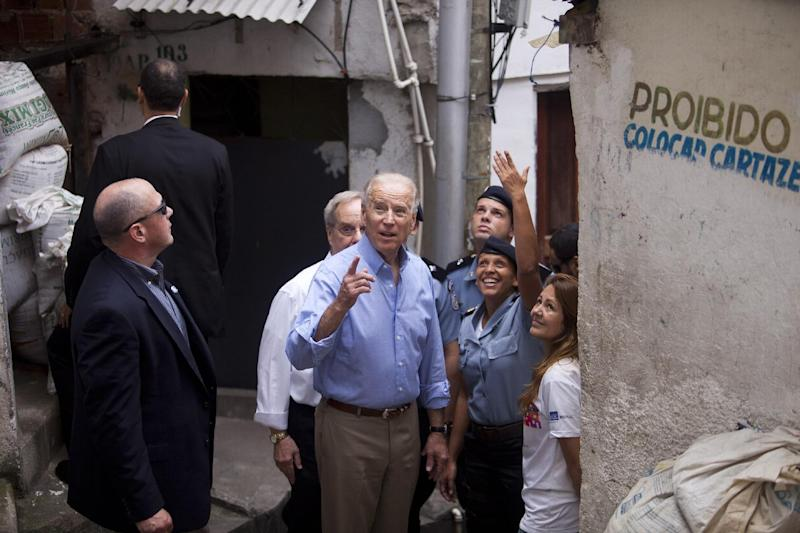 U.S. Vice President Joe Biden, center, speaks with Pacification Unit Major Priscilla Azevedo, gesturing second from right, during his visit to the Santa Marta slum in Rio de Janeiro, Brazil,  Thursday, May 30, 2013. Biden is wrapping up his visit to Rio de Janeiro with a visit to a slum before traveling to Brasilia for a Friday meeting with Brazilian President Dilma Rousseff.  (AP Photo/Victor R. Caivano)