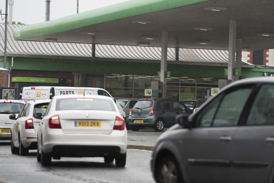Vehicles wait to fill up at a petrol station in Manchester, England, Monday, Sept. 27, 2021. British Prime Minister Boris Johnson is said to be considering whether to call in the army to deliver fuel to petrol stations as pumps ran dry after days of panic buying. ( AP Photo/Jon Super)