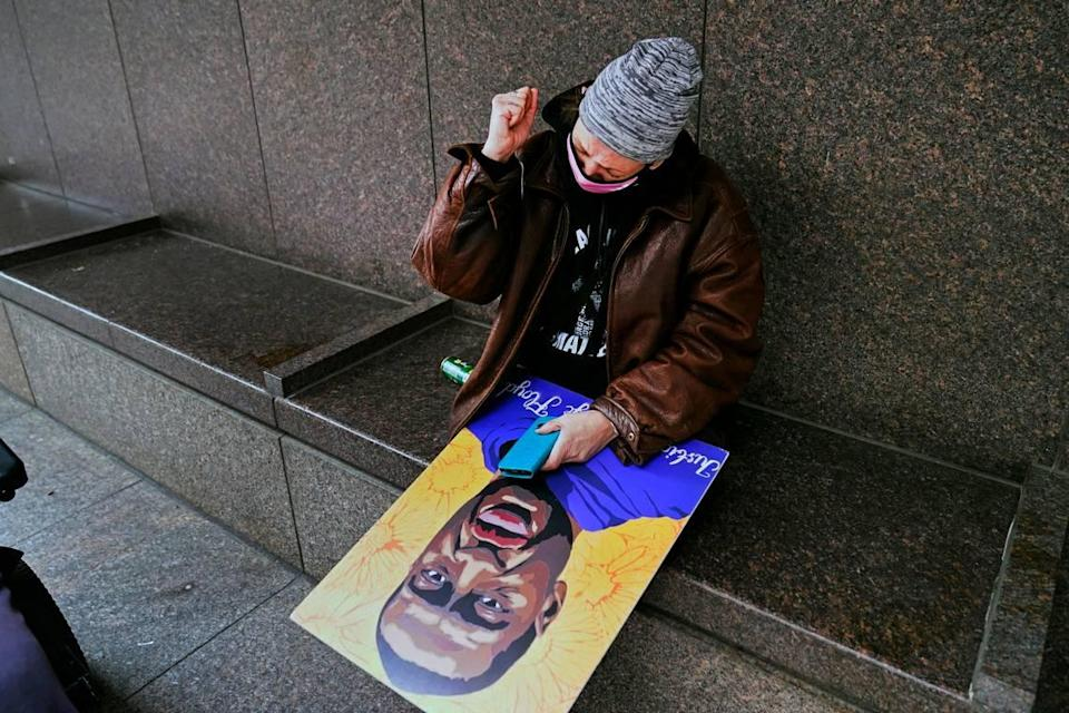 A woman holding a George Floyd poster pumps her fist across the street from the Hennepin County Government Center in Minneapolis on Tuesday after jurors found former police Officer Derek Chauvin guilty on all counts of murder and manslaughter in Floyd's death last May.