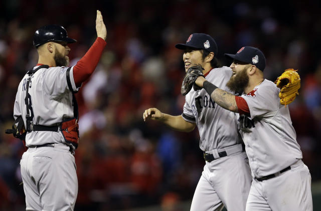 Boston Red Sox's Koji Uehara, catcher David Ross and Mike Napoli (12) celebrate after Game 4 of baseball's World Series against the St. Louis Cardinals Sunday, Oct. 27, 2013, in St. Louis. The Red Sox won 4-2 to ties the series at 2-2.(AP Photo/Jeff Roberson)