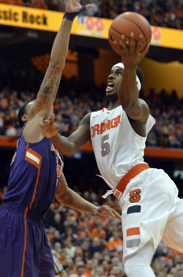 Syracuse's C.J. Fair, right, drives against Clemson's K. J. McDaniels during the second half of an NCAA college basketball game in Syracuse, N.Y., Sunday, Feb. 9, 2014. Syracuse won 57-44. (AP Photo/Kevin Rivoli)
