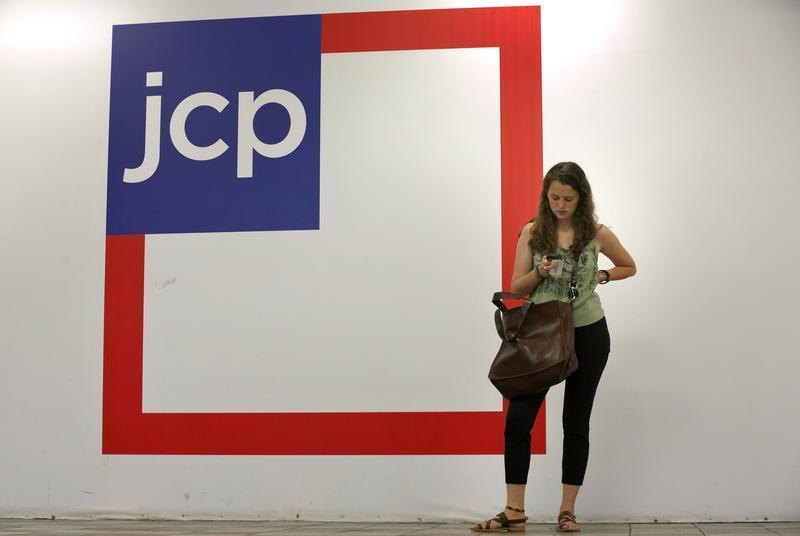 Woman checks her phone outside the entrance of a J.C. Penney store in New York