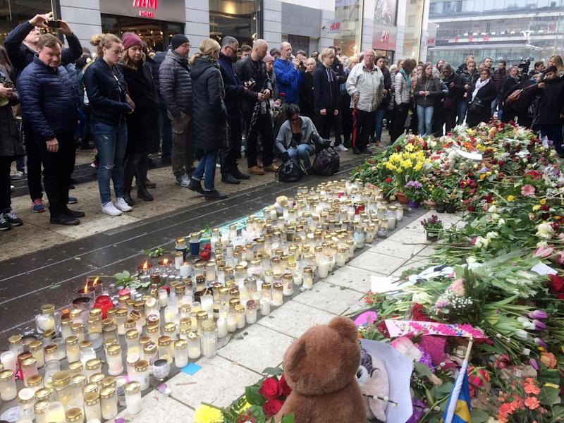 Thousands have shown up to honour the victims of the Stockholm attack, lining the street outside the Ahlens department store with candles and flowers (Reuters)