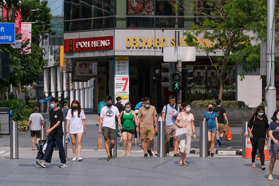 SINGAPORE - 2021/05/16: People wearing face masks as a preventive measure against the spread of covid-19 walk across a Street in Singapore. Singapore tightens its Covid-19 restrictions from May 16 to June 13 due to the rise of Covid-19 cases in the community. During this time, only groups of 2 people outside will be allowed, malls and attractions are to reduce capacity, and dining-in at eateries are prohibited. (Photo by Maverick Asio/SOPA Images/LightRocket via Getty Images)