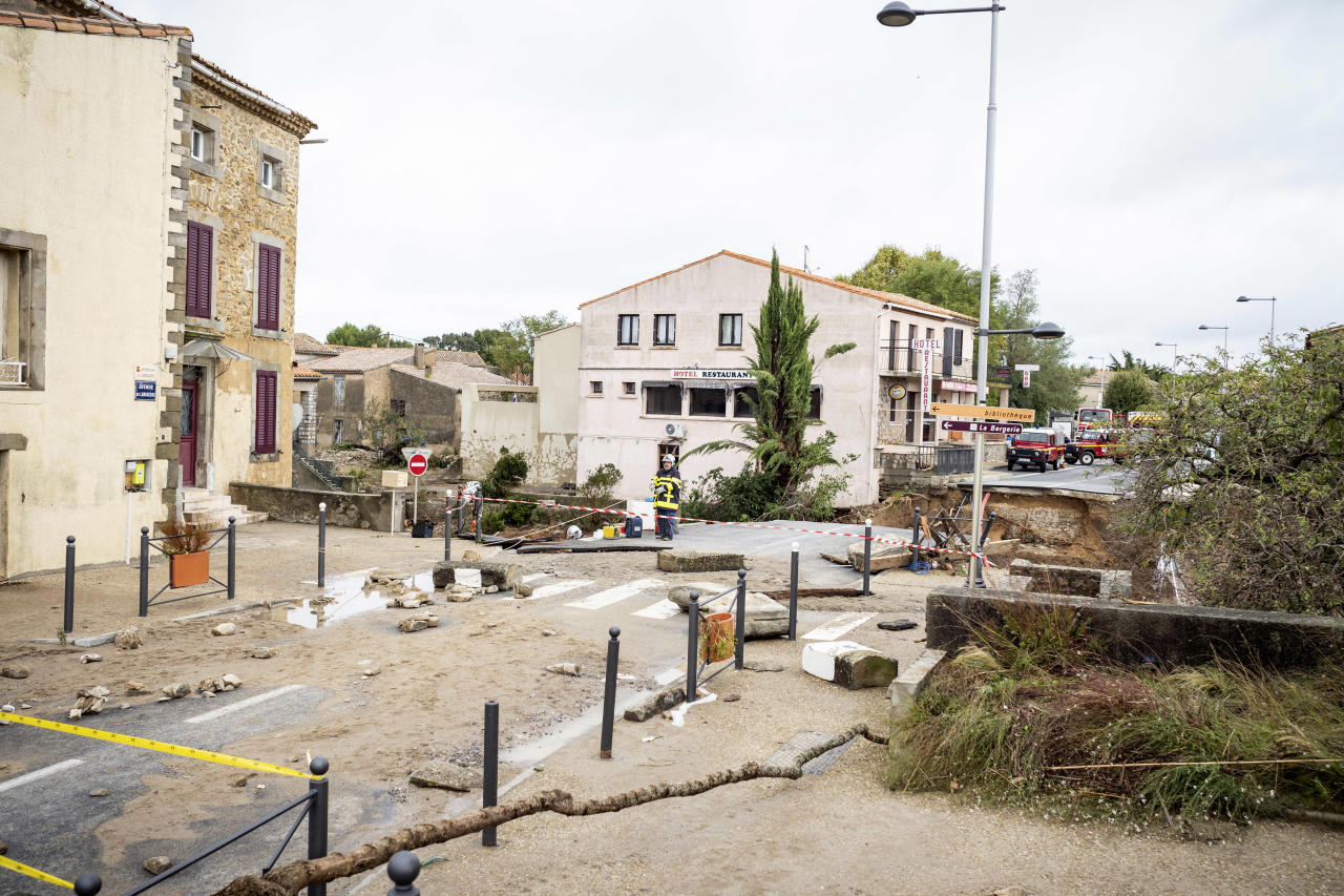 <p>Rescue workers, background, secure the area by a collapsed bridge in the town of Villegailhenc, southern France, Monday, Oct.15, 2018. (Photo: Fred Lancelot/AP) </p>