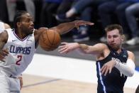 Los Angeles Clippers forward Kawhi Leonard (2) defends as Dallas Mavericks guard Luka Doncic, right, makes a pass in the second half in Game 3 of an NBA basketball first-round playoff series in Dallas, Friday, May 28, 2021. (AP Photo/Tony Gutierrez)