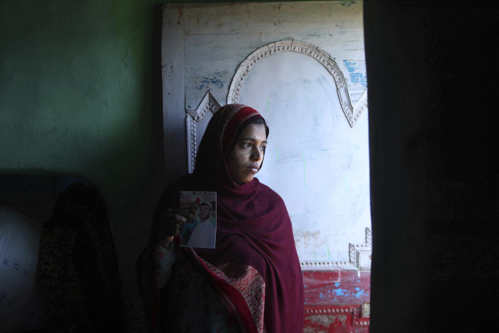 Safina Bi, who alleges her husband Altaf Hussain was killed by Pakistan army while ferrying ration supplies to one of the Indian army border posts, stands holding a picture of her husband at her house in Poonch, India, Wednesday, Dec. 16, 2020. The terrain is tough and the life of civilians living in the area is even tougher, with them often caught in the line of fire along the Line of Control, that for the past 73 years divided the region between the two nuclear-armed rivals of India and Pakistan. Over the last year, troops from the two sides have traded fire almost daily along the frontier, leaving dozens of civilians and soldiers dead. (AP Photo/Channi Anand)