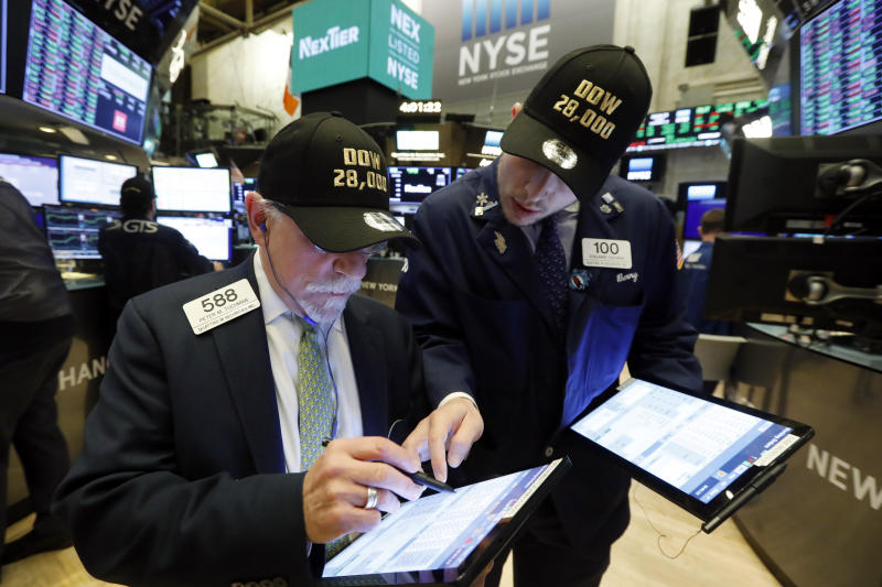"Traders Peter Tuchman, left, and his son Benjamin Tuchman, wear ""Dow 28,000"" hats at the close of trading on the floor of the New York Stock Exchange, Friday, Nov. 15, 2019. (AP Photo/Richard Drew)"