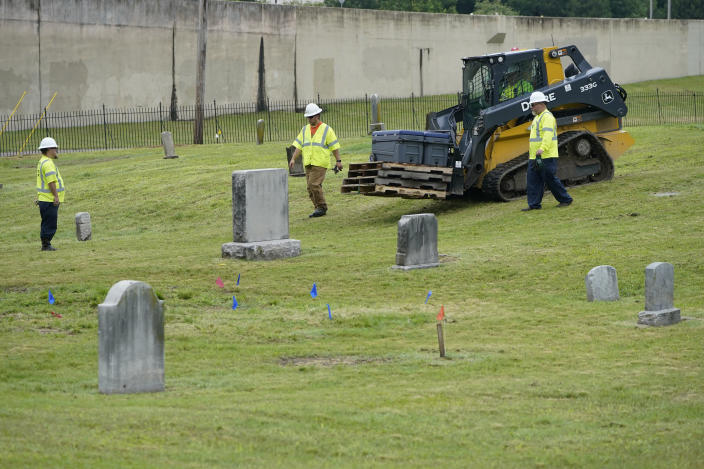 Workers bring equipment to the site where excavation will take place at Oaklawn Cemetery in a search for victims of the Tulsa Race Massacre believed to be buried in a mass grave, Tuesday, June 1, 2021, in Tulsa, Okla. (AP Photo/Sue Ogrocki)