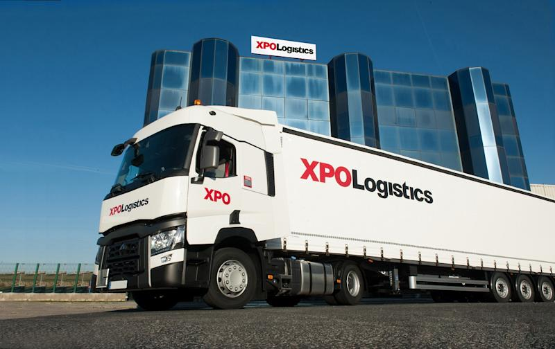 Truck in front of tall office building, both with XPO Logistics logos on them.