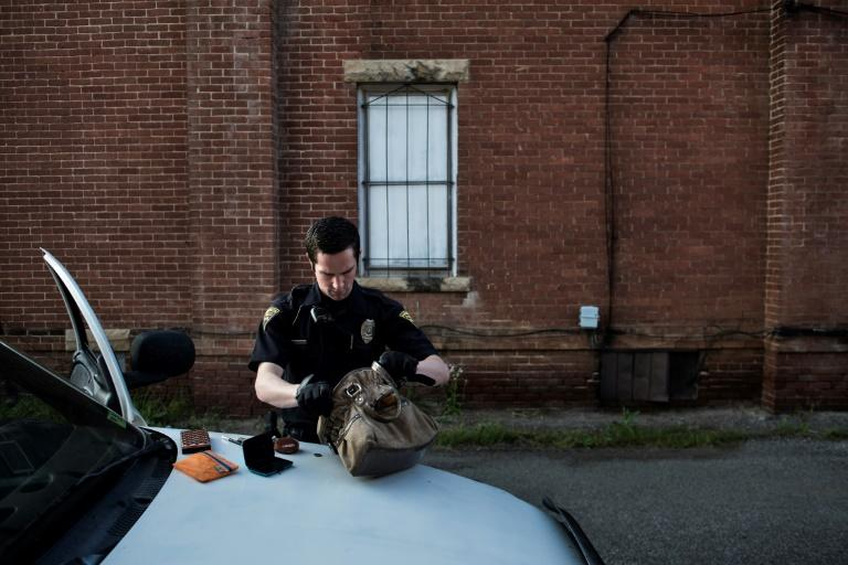 Police officer searches the purse of a suspected prostitute in Huntington, West Virginia, a place where those looking for hope leave and those without turn to drugs