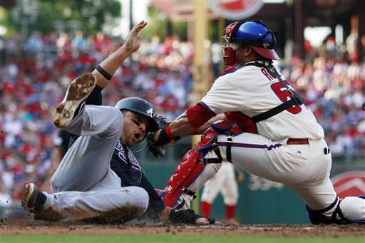 Atlanta Braves' Martin Prado, left, scores past the tag of Philadelphia Phillies catcher Carlos Ruiz on a three-run double by Jason Heyward in the second inning of a baseball game on Saturday, Sept. 22, 2012, in Philadelphia. (AP Photo/Matt Slocum)