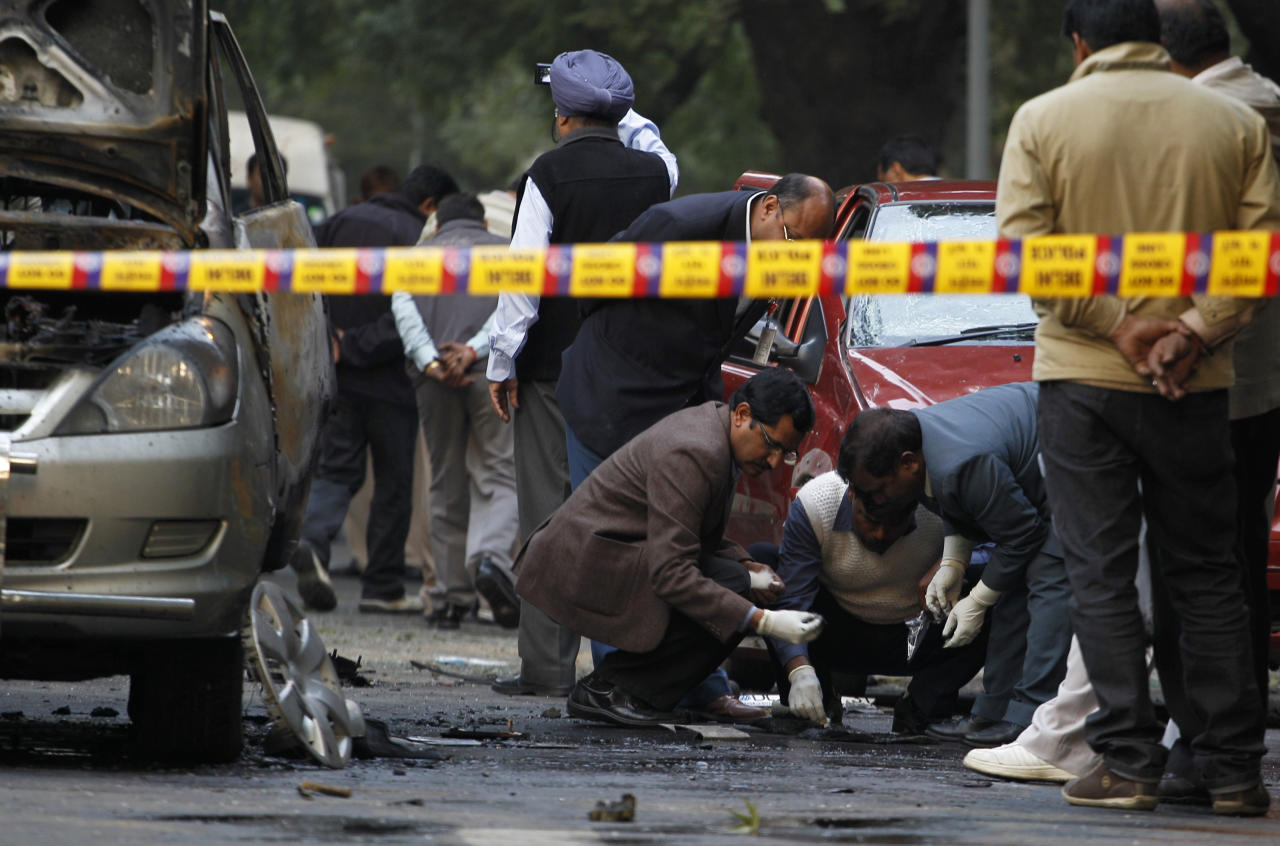Indian security and forensic officials examine the site after an explosion tore through a car belonging to the Israel Embassy, left, in New Delhi, India, Monday, Feb. 13, 2012. The driver and a diplomat's wife were injured, according to Indian officials. (AP Photo/Saurabh Das)