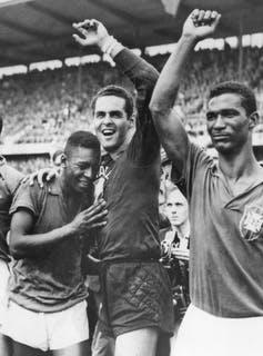 A man embraces two soccer players, their arms raised in victory.