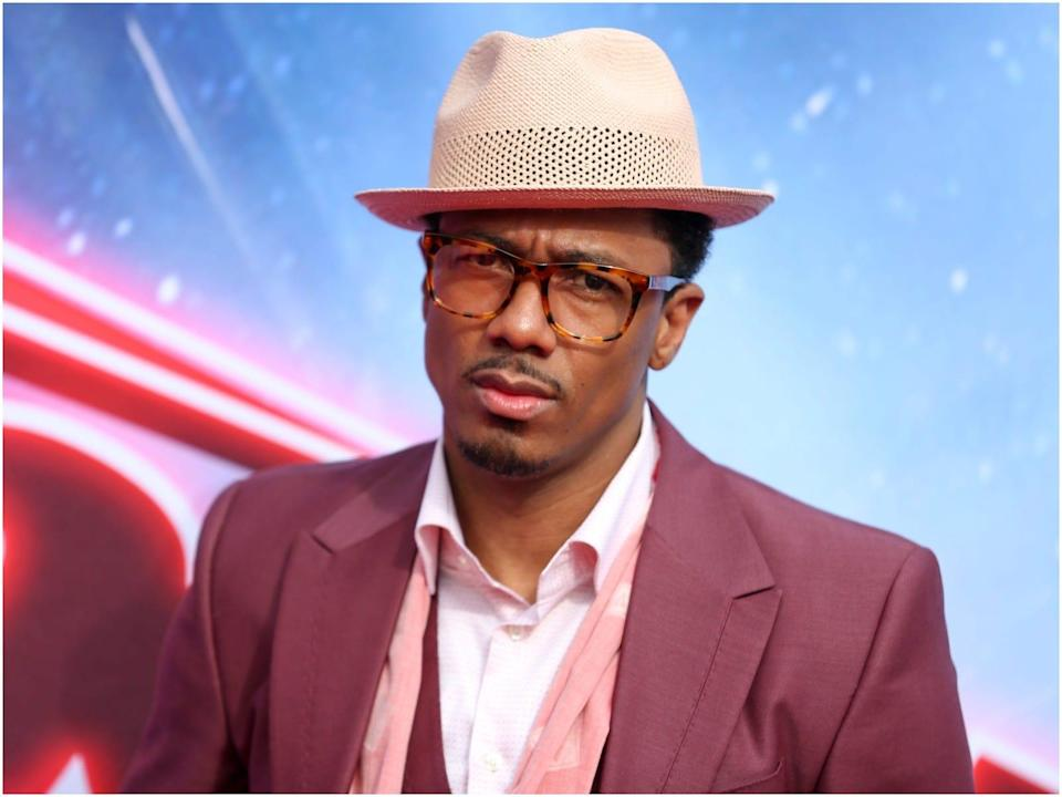 Nick Cannon wearing a tan hat and a pink suit.