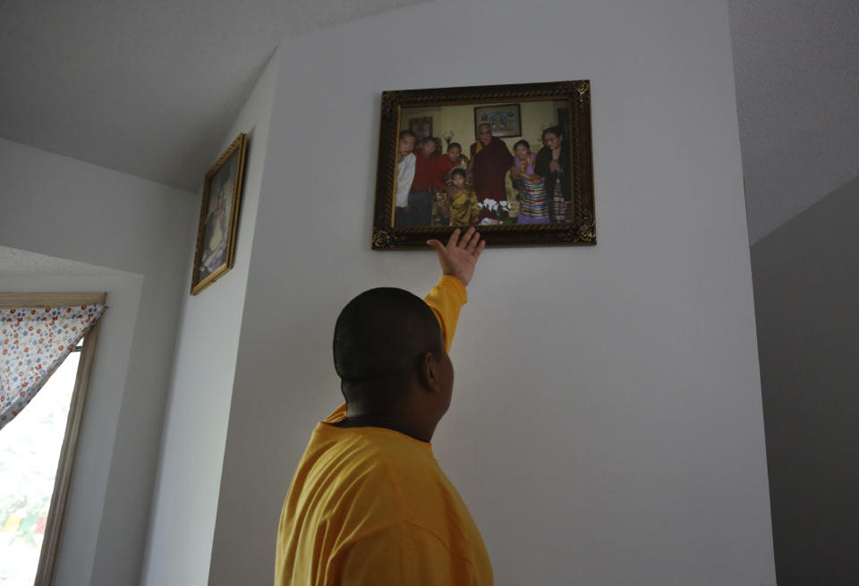 Jalue Dorje, 14, points to a photograph of his family with the Dalai Lama that hangs in the entryway of his family's home in Columbia Heights, Minn., on Tuesday, July 20, 2021. When he was an infant, Jalue, now 14, was identified as the eighth reincarnation of the lama Terchen Taksham Rinpoche. After finishing high school in 2025, Jalue will head to northern India and join the Mindrolling Monastery, more than 7,200 miles (11,500 kilometers) from his home. (AP Photo/Jessie Wardarski)