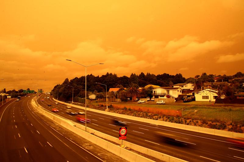 Pictured are orange skies over a highway in Auckland caused by the Australian bushfires.