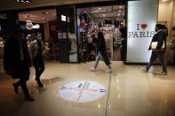 People walk in a shopping mall Monday, May 11, 2020 in Paris. The French began leaving their homes and apartments for the first time in two months without permission slips as the country cautiously lifted its lockdown. Clothing stores, coiffures and other businesses large and small were reopening on Monday _ with strict precautions to keep the coronavirus at bay. (AP Photo/Francois Mori)