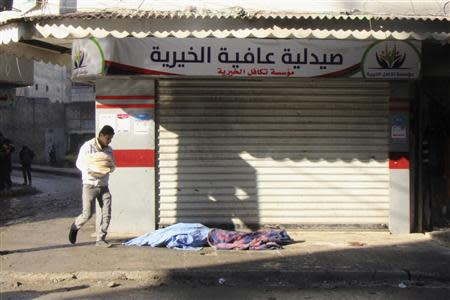 A man carrying bread walks past covered dead bodies lying on the ground after what activists said was an air raid by forces loyal to Syrian President Assad, at Masaken Hanano in Aleppo