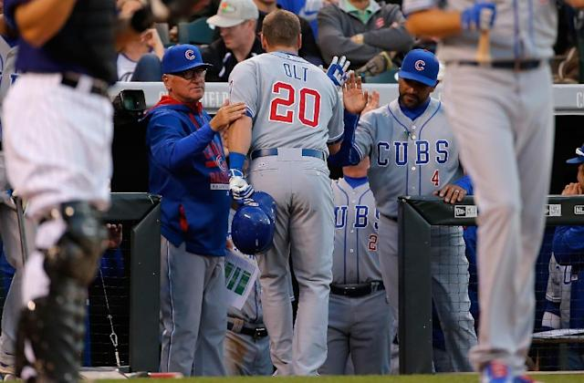 The Chicago Cubs bench coach Dave Martinez welcomes Mike Olt to the dugout during a MLB game in Denver, Colorado, in 2015 (AFP Photo/DOUG PENSINGER)
