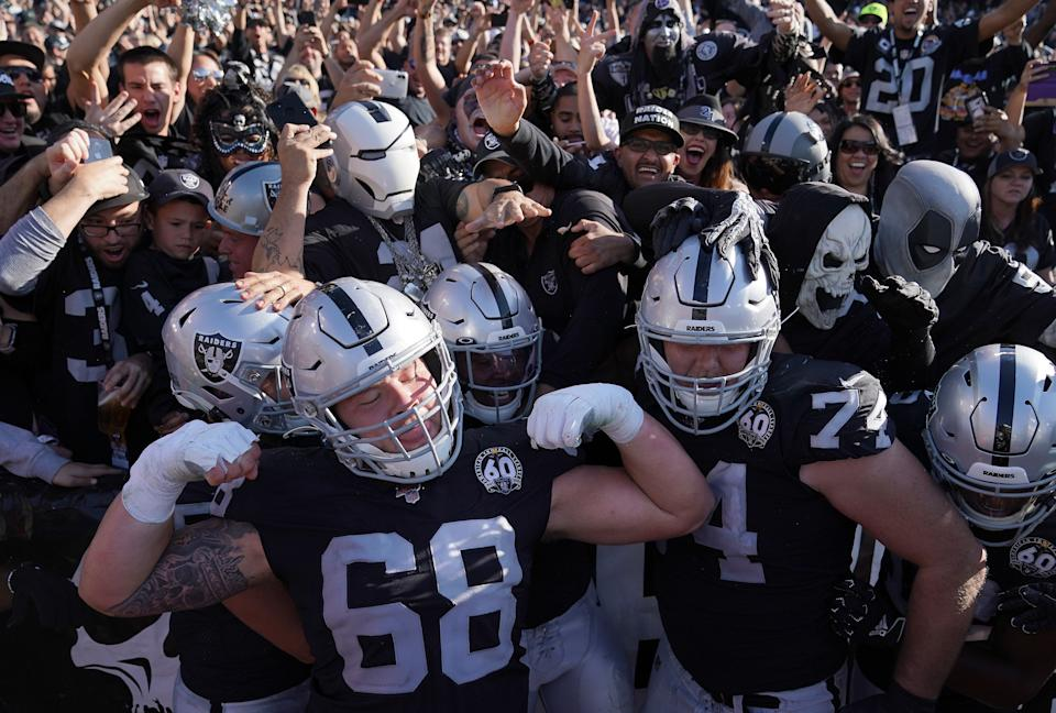 "Josh Jacobs (28), Andre James (68), and Kolton Miller (74) of the Oakland Raiders celebrates with fans in the ""Black Hole"" after Jacobs scored against the Detroit Lions. (Photo by Thearon W. Henderson/Getty Images)"