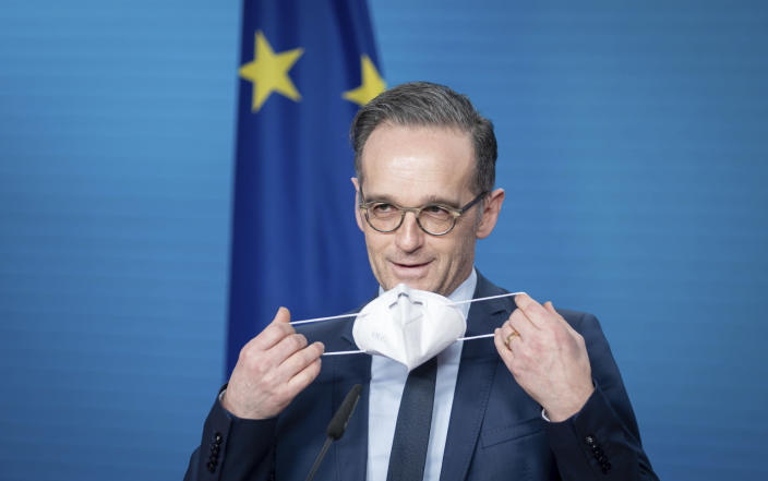 Heiko Maas, German Foreign Minister, puts on his mouth-nose protection at the end of the press conference on the informal virtual meeting of the foreign ministers of the member states of the Vienna nuclear agreement in Berlin, Germany, Monday, Dec. 21, 2020. (Kay Nietfeld/dpa via AP)