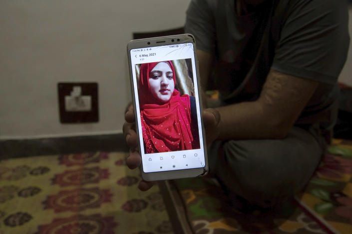Shahid Nazir Bhat, a Muslim, displays a photograph of Manmeet Kour Bali, a Sikh by birth who converted to Islam to marry him, in Srinagar, India, July 8, 2021. (Showkat Nanda/The New York Times)