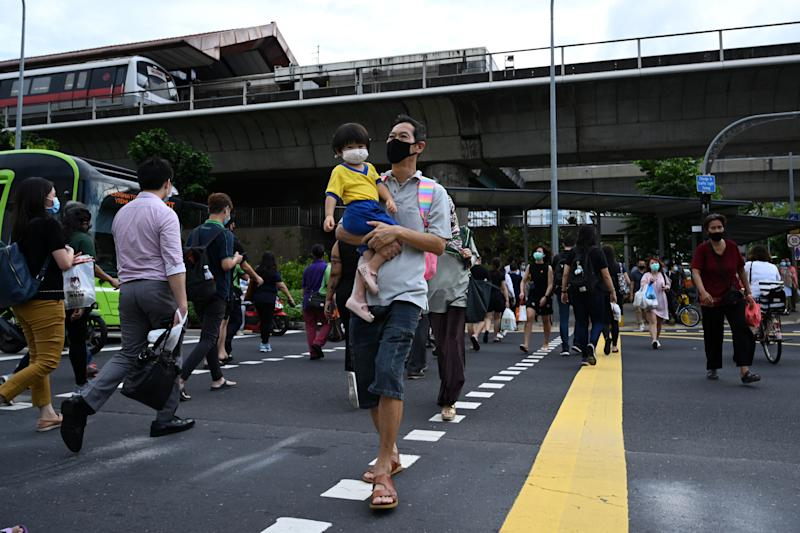 """A man with a child crosses a street in Singapore on June 23, 2020. - Singapore's Prime Minister Lee Hsien Loong called a general election """"like no other"""" on June 23 as the city-state struggles to recover from a major coronavirus outbreak that has swept through crowded migrant worker dormitories. (Photo by Roslan RAHMAN / AFP) (Photo by ROSLAN RAHMAN/AFP via Getty Images)"""