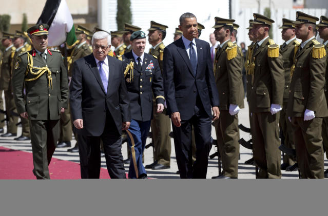 President Barack Obama, right, and Palestinian President Mahmoud Abbas, front left, walk along to red carpet for a troop review during an arrival ceremony as Obama arrives at the Muqata Presidential Compound Thursday, March 21, 2013, in the West Bank town of Ramallah. (AP Photo/Carolyn Kaster)
