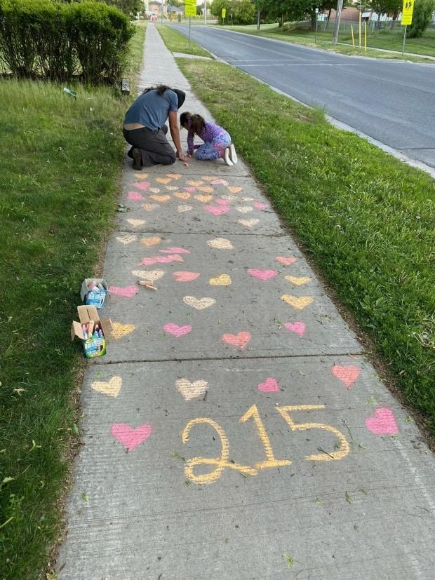 Joseph Pitawanakwat and his daughter Ruth draw chalk hearts in front of their house.  (Submitted by Kristy Pitawanakwat - image credit)