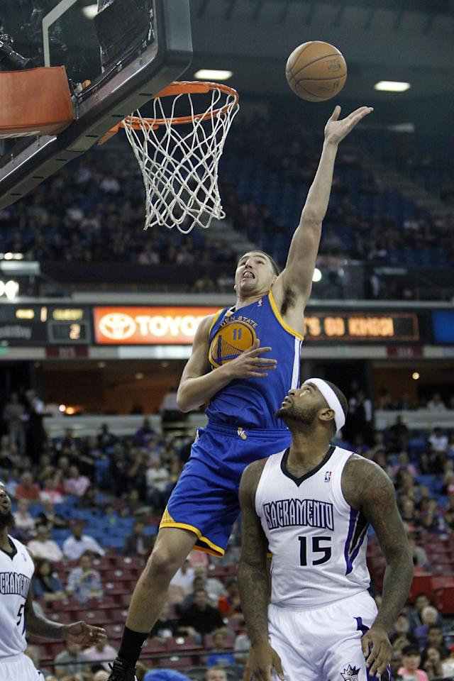 Golden State Warriors guard Klay Thompson, top, goes to the basket against Sacramento Kings center DeMarcus Cousins during the first quarter of an NBA preseason basketball game in Sacramento, Calif., Wednesday, Oct. 23, 2013. (AP Photo/Rich Pedroncelli)