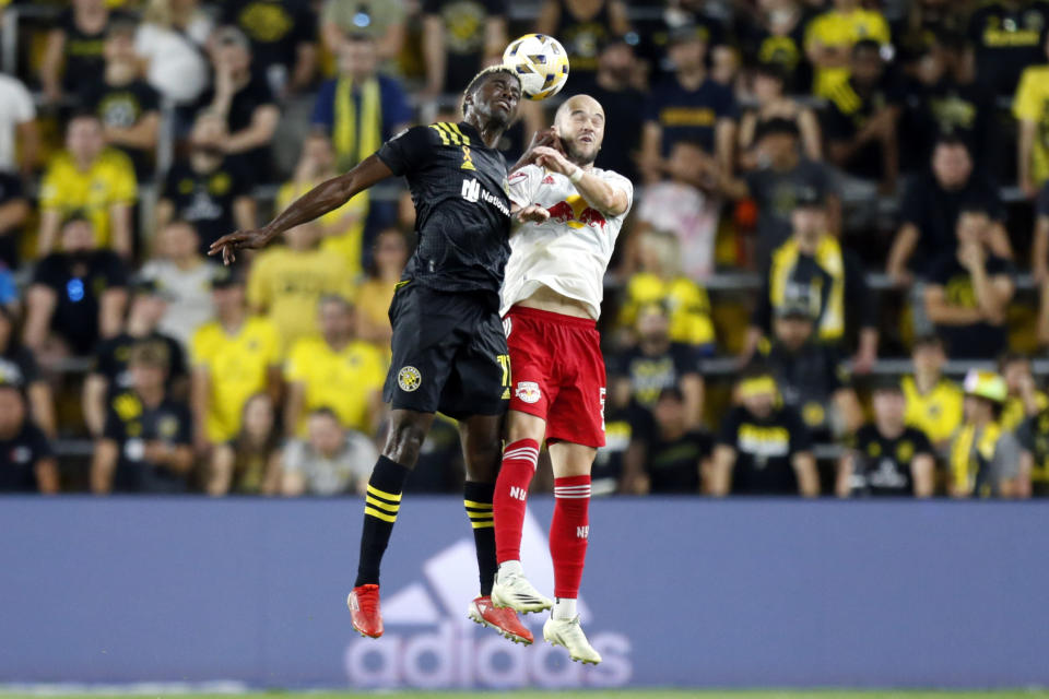 Columbus Crew forward Gyasi Zardes, left, heads the ball in front of New York Red Bulls defender Andrew Gutman during an MLS soccer match in Columbus, Ohio, Tuesday, Sept. 14, 2021. The Crew won 2-1. (AP Photo/Paul Vernon)