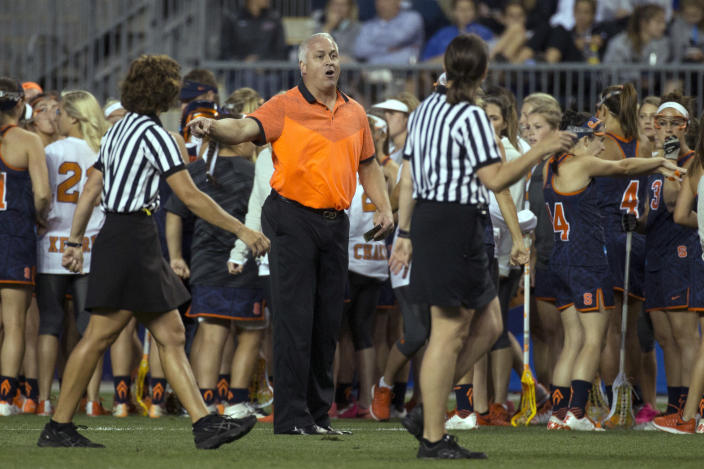 FILE - In this Friday, May 22, 2015, file photo, Syracuse head coach Gary Gait, center, talks with he officials during the first half of the semifinals in the NCAA Division I women's lacrosse tournament against the Maryland, in Chester, Pa. Gait, who has coached the Syracuse women's lacrosse team for the past 14 years and built the program into a national power, will succeed current men's coach John Desko, who announced his retirement Monday, June 7, 2021, after 22 seasons and five national championships. (AP Photo/Chris Szagola, File)